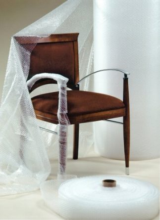 a bubble wrap roll next to a chair demonstrating that it can be used to protect the material